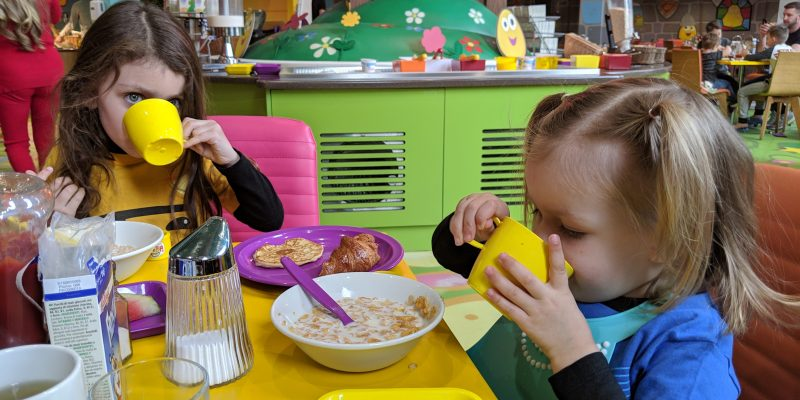 two kids eating breakfast in a colorful restaurant